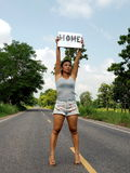 Female hitchhiker on a deserted road Royalty Free Stock Image