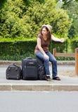 Hitchhiking, discouragement. Woman making hitchhiking sitting on his suitcases, discouragement Royalty Free Stock Photo