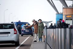 Old pleasant man and woman are stopping car. Hitchhiking. Full length of stylish senior couple is standing near road and trying to catch transport. Gentleman is Royalty Free Stock Photos