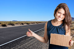 Hitchhiking Girl. Young woman hitch hiking at a desert road holding a cardboard Royalty Free Stock Images