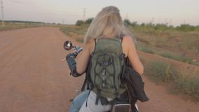 Hitchhiking girl sits down to the motorcyclist. At sunset stock video