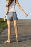 Hitchhiking girl on the street Stock Images
