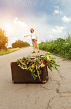 Hitchhiking adventure. Hitchhiking girl traveler with old suitcase Royalty Free Stock Photos