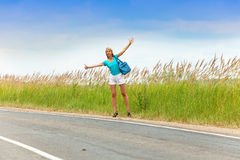 Hitchhiking girl votes on road Royalty Free Stock Photos