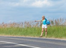 Hitchhiking girl votes on road Stock Image