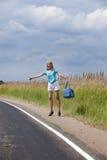 Hitchhiking girl votes on road Stock Photo
