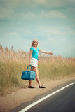 Hitchhiking girl votes on road Stock Photos