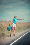 Hitchhiking girl votes on road Stock Photo
