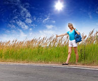 Hitchhiking girl votes on road.Portrait in a sunny day Royalty Free Stock Images