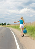 Hitchhiking girl votes on road Royalty Free Stock Image