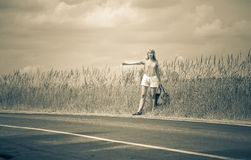 Hitchhiking girl votes on road,with retro effect Royalty Free Stock Images