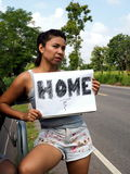 Female hitchhiker wearing denim shorts stock image