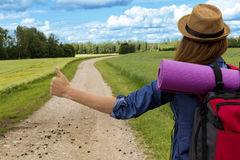 Hitchhiking road travel. Woman with a big backpack trying to stop a ride. By thumbing Stock Photography