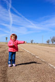 Hitchhiker. Small child with a pink coat hitchhiking on a desolate road Royalty Free Stock Photo