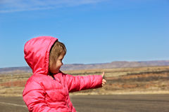 Hitchhiking. Small child with a pink coat hitchhiking on a desolate road Stock Photo