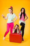 Hitchhiking. Three girls hitchhike together, red suitcase, yellow background Royalty Free Stock Image