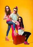 Hitchhiking. Three girls hitchhike together, red suitcase, yellow background Royalty Free Stock Images