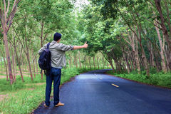 Hitchhiking tourism concept. Travel hitchhiker man carrying back Royalty Free Stock Image