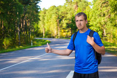 Hitchhiking traveler try to stop car on forest road Royalty Free Stock Photos