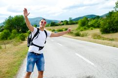 Hitchhiking traveler try to stop car on the mountain road.  Stock Photography