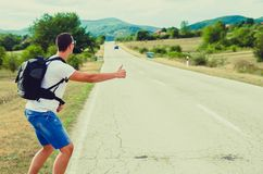 Hitchhiking traveler try to stop car on the mountain road. Nature and travel concept. Hitchhiking traveler try to stop car on the mountain road Royalty Free Stock Photography
