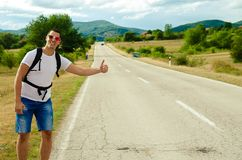 Hitchhiking traveler try to stop car on the mountain road. Travel concept. Hitchhiking traveler try to stop car on the mountain  road Stock Photos