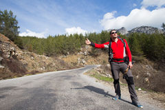 Hitchhiking traveler try to stop car on the mountain road. Sport, people Royalty Free Stock Image
