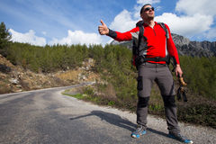 Hitchhiking traveler try to stop car on the mountain road. Sport, people Royalty Free Stock Images