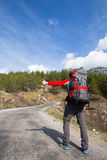 Hitchhiking traveler try to stop car on the mountain road. Sport, people Stock Images