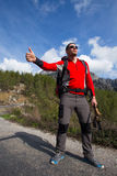 Hitchhiking traveler try to stop car on the mountain road. Sport, people Royalty Free Stock Photos