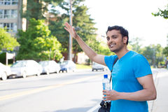 Hitchhiking or waving. Closeup portrait, young man in blue shirt carrying water bottle and black bag, raising hand to hitchhike, flag or hail a cab, isolated Stock Photos