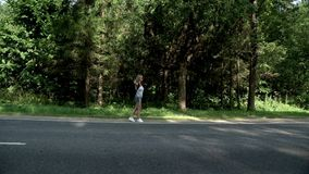 Hitchhiking woman with backpack on road on fores background. Cute woman with backpack and sunglasses hitch hiking on road. Young woman traveler with backpack stock footage