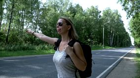 Hitchhiking woman with backpack standing on road. Cute young woman with backpack and sunglasses hitch hiking car on road. Young woman traveler with backpack stock video