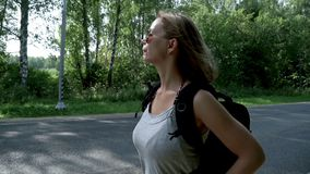 Hitchhiking woman with backpack standing on road waiting for a passing car. Cute woman with backpack and sunglasses hitch hiking car on road. Young woman stock footage