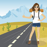 Hitchhiking woman with backpack and sunglasses standing on highway in mountains. Adventure and tourism concept. Stock Image