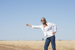 Hitchhiking woman at country road Stock Images