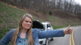 Hitchhiking woman gives a thumbs up to the camera ALT stock video footage