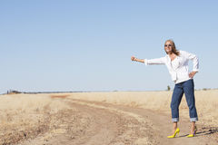 Hitchhiking woman in high heels at dirt road Royalty Free Stock Photography