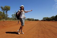 Hitchhiking Woman in Outback. A mature woman dressed up in bright coloured clothes and high heel shoes is waiting for a lift on a remote dirt road in Outback Stock Photo