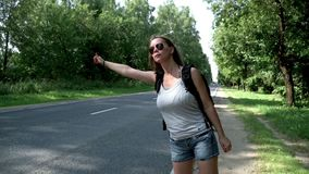 Hitchhiking woman traveler with backpack standing on road on summer day. Hitchhiking woman traveler with backpack standing on road. Cute young woman with stock video footage
