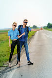 Hitchhiking young couple. Hitchhiking couple. Happy young people standing on a highway Stock Photography