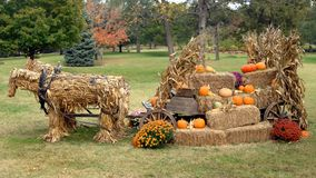Hitchin' A Ride. Awesome harvest display shows two corn shuck horses pulling a wagon loaded with hay bales and pumpkins Stock Image