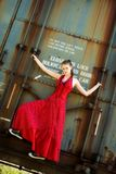 Hitching a Ride in Style. Beautiful young girl in an evening gown and sneakers hanging onto a rusty old boxcar Royalty Free Stock Photography