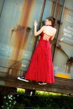 Hitching a Ride in Style. Beautiful young girl in an evening gown and sneakers hanging onto a rusty old boxcar stock photography