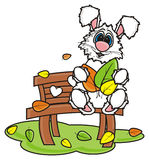 Hite rabbit sitting on a bench and holding colorful leaves Royalty Free Stock Photo