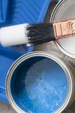 Hite und blaue Farbe in den Dosen und in der Bürste Stockfotos