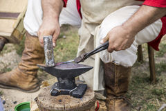 Hiting melting metal. Blacksmith making a small envelop opener knife Royalty Free Stock Image