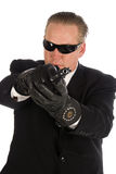 Hitman. Hitman wearing a suit and sunglasses pointing a gun straight at the camera royalty free stock image