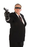 Hitman with gun. Hitman wearing a suit and sunglasses pointing his gun out in front of him. Isolated on white Royalty Free Stock Images
