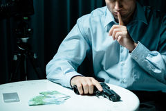 Hitman with gun and money. Image of hitman with gun and money in dark room Royalty Free Stock Photo